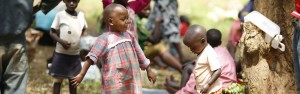 A young girl smiles while others are running around
