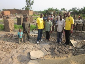 A group of people standing near several piles of bricks