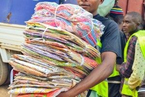 A man carries a large stack of donated clothing packages