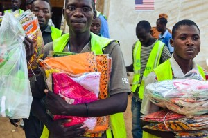 A few men in neon green vests carry donated clothing packages