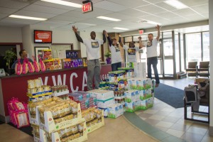 Volunteers jump up and celebrate around a large pile of donated goods