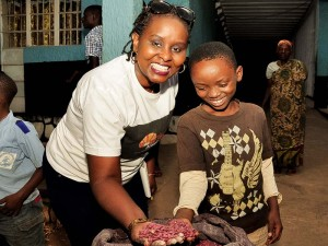 Aline and a young boy holding a handful of beans together