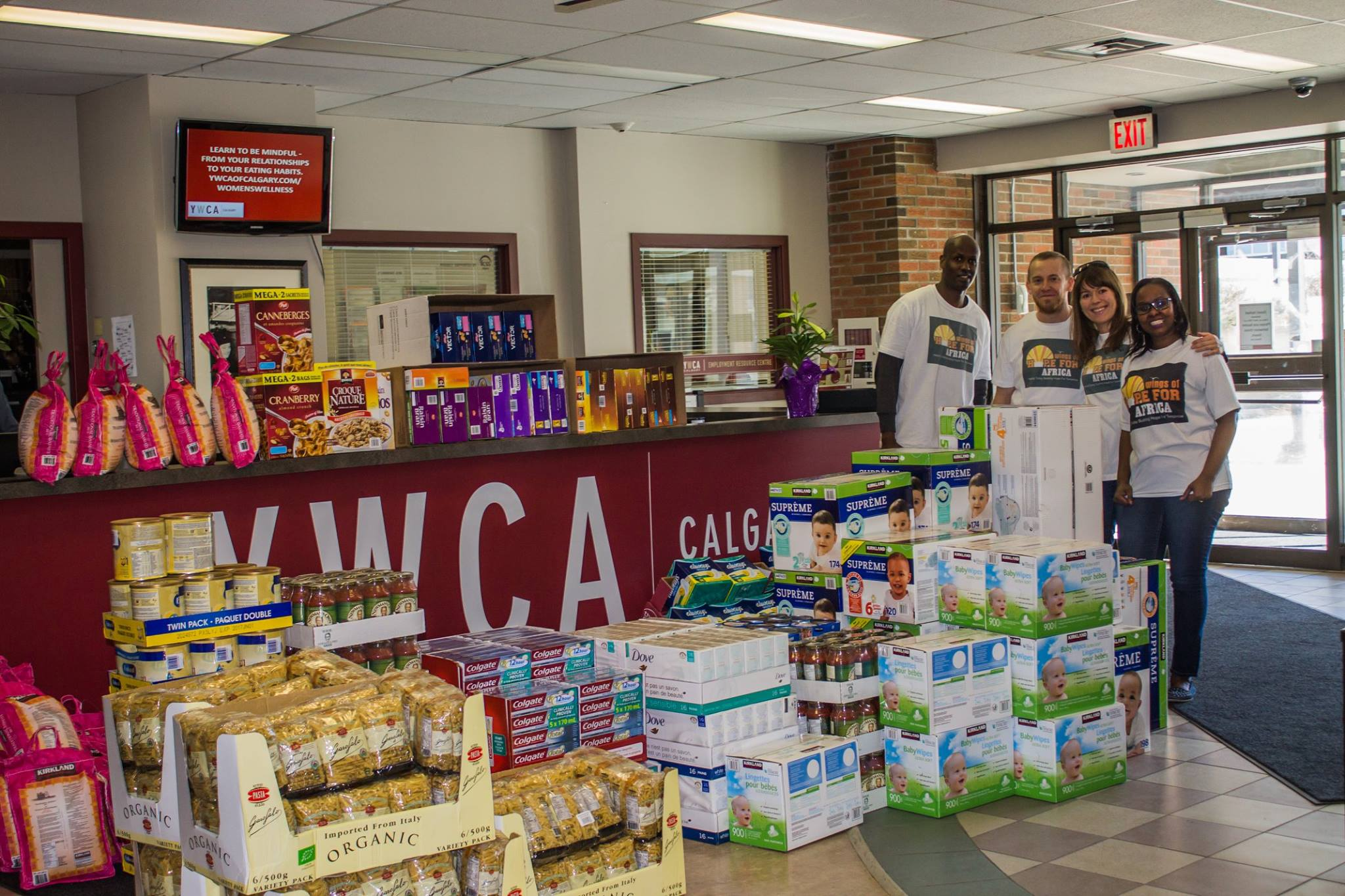 A group of volunteers stand by a large amount of donated goods