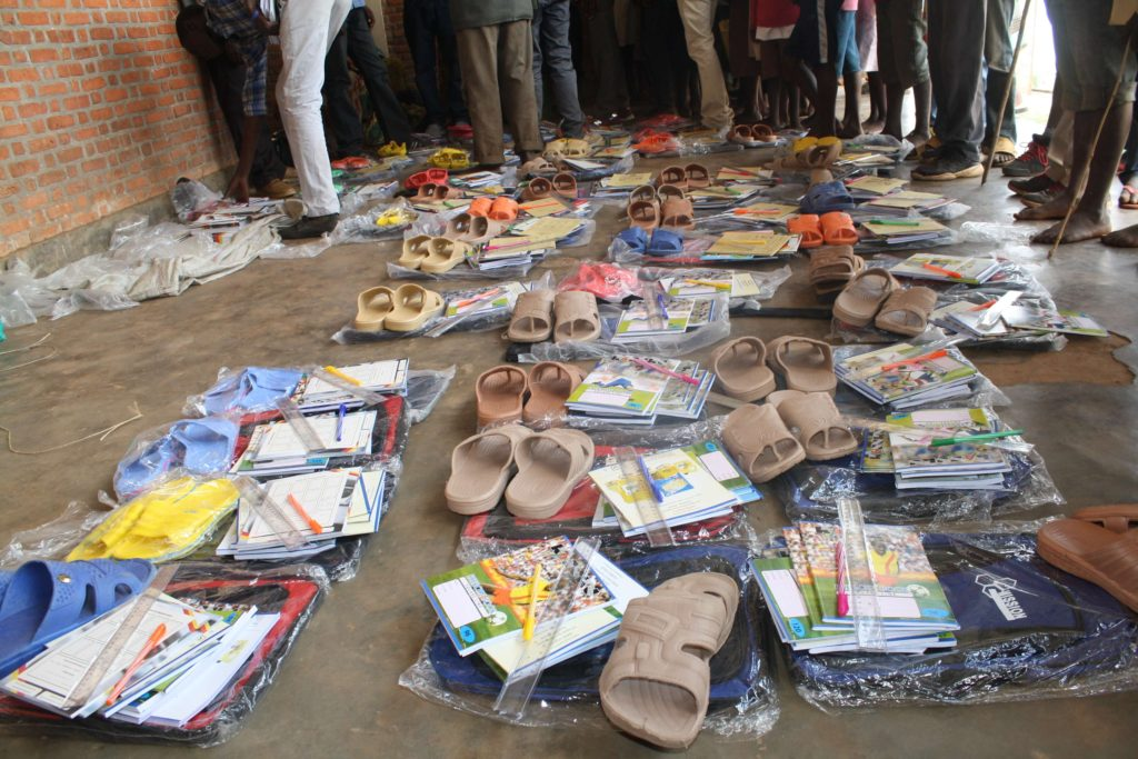 Several care packages on the ground containing various goods such as pens, notebooks, and sandals