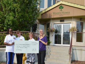 A group of 4 women hold a cheque for Wood's Homes Foundation for $5000