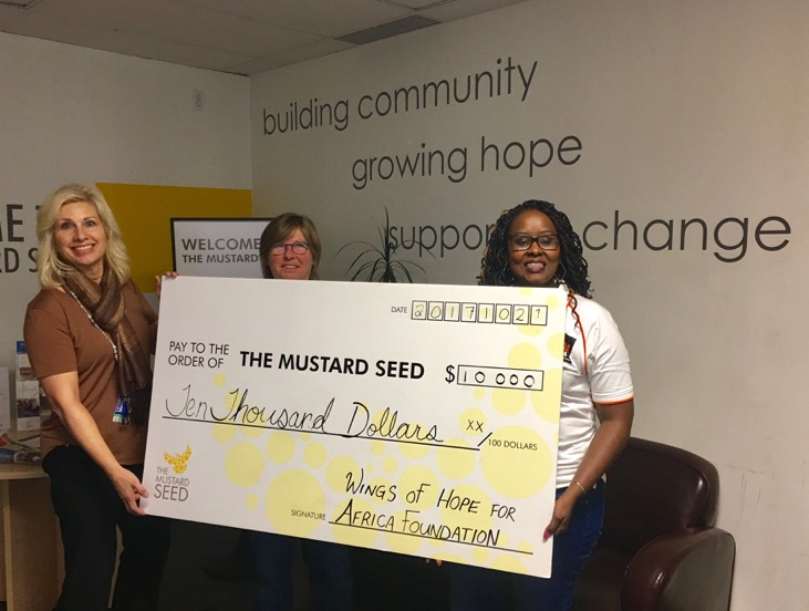 3 women holding a Mustard Seed Donation Cheque for $10,000