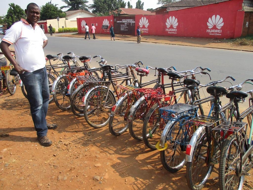 A man stands by a line up of bicycles