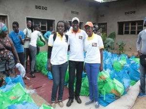 3 people posing in the foreground with gift bags surrounding them