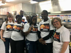 A group of volunteers posing inside of a kitchen