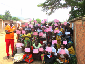 A large group of people holding pink health care cards