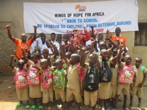 A large group of young men and children wearing backpacks standing in front of a large banner