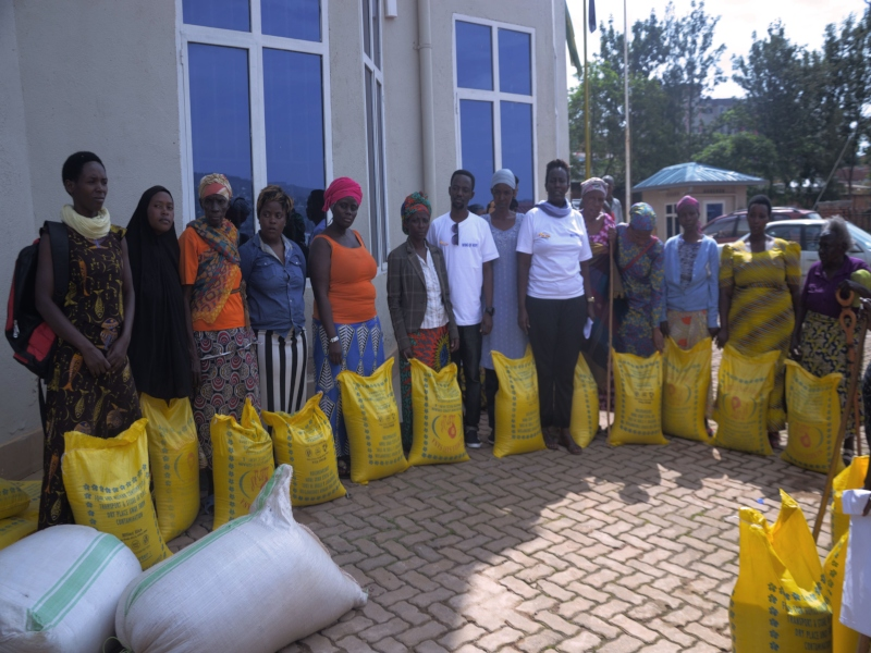 A large group of woman in a half circle arrangement standing with several large yellow bags of rice