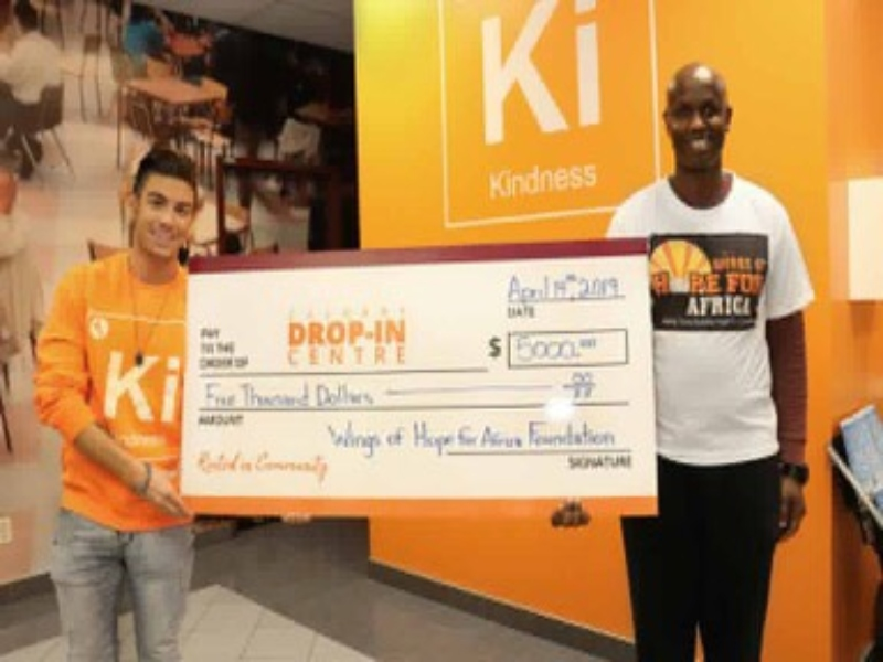 Two men holding a large award cheque for $5000